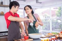 Pares novos asiáticos Sorrindo, cozinhando assim o divertimento prepare a salada para o alimento junto felizmente fotos de stock royalty free