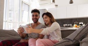 Pares novos atrativos da raça misturada usando o tablet pc, mulher asiática do homem latino-americano feliz que senta-se junto no video estoque
