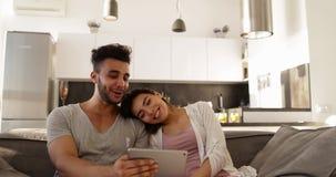 Pares novos atrativos da raça misturada usando o tablet pc, mulher asiática do homem latino-americano feliz que senta-se junto no filme