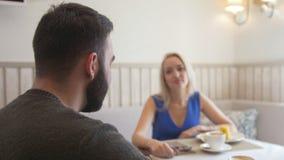 Pares novos atrativos que falam ao apreciar uma xícara de café no café vídeos de arquivo