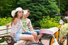 Pares novos atrativos que sentam-se no banco perto das bicicletas no parque Fotos de Stock