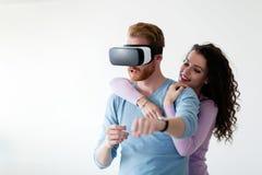 Pares novos atrativos que tentam auriculares da realidade virtual Fotografia de Stock