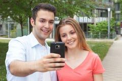 Pares novos atrativos que tomam um selfie com telefone celular Fotografia de Stock Royalty Free