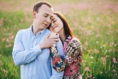Pares novos bonitos delicadamente que abraçam e que beijam na luz do sol no prado fresco da mola com flores cor-de-rosa Família à foto de stock royalty free