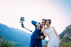 Pares novos bonitos do casamento que fazem o selfie no fundo das montanhas foto de stock