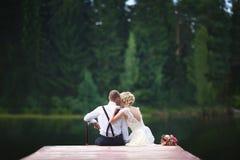 Pares novos bonitos do casamento que sentam-se no cais fotos de stock royalty free