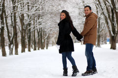 Pares novos bonitos em um parque nevado envolvido foto de stock