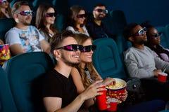 Pares novos bonitos em uma data no cinema Fotografia de Stock Royalty Free