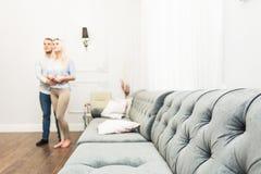 Pares novos bonitos em uma sala de visitas com um interior moderno imagem de stock royalty free