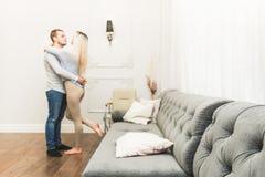 Pares novos bonitos em uma sala de visitas com um interior moderno cara a cara fotografia de stock royalty free