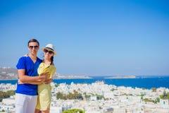 Pares novos bonitos na ilha de Mykonos, Cyclades Os turistas apreciam suas férias gregas no fundo de Grécia famoso Imagem de Stock