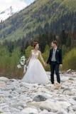 Pares novos bonitos nas montanhas Caminhada do casamento nas montanhas fotografia de stock royalty free