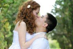 Pares novos bonitos no amor em uma clareira verde Fotos de Stock