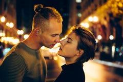 Pares novos bonitos no amor que beija na rua da cidade da noite fotos de stock