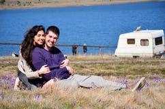 Pares novos bonitos que abraçam e que sentam-se em um prado da mola com açafrões Foto de Stock