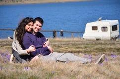 Pares novos bonitos que abraçam e que sentam-se em um prado da mola com açafrões Fotografia de Stock Royalty Free