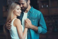 Pares novos bonitos que abraçam em seu apartamento novo Imagem de Stock Royalty Free