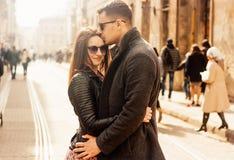 Pares novos bonitos que abraçam na rua fotografia de stock