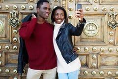 Pares novos bonitos que andam em um homem e em uma mulher de cidade parados para tomar uma imagem com Smart-telefone Imagens de Stock Royalty Free