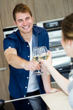 Pares novos bonitos que brindam com vidros de vinho branco na cozinha Imagem de Stock Royalty Free
