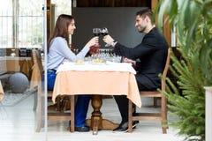 Pares novos bonitos que brindam vidros de vinho no restaurante Imagem de Stock Royalty Free