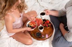 Pares novos bonitos que comem o café da manhã na cama Foto de Stock Royalty Free