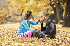 Pares novos bonitos que descansam e que beijam após o treinamento bem sucedido no parque Imagem de Stock Royalty Free