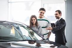 Pares novos bonitos que escolhem um carro no negócio que fala ao gerente do salão de beleza com a tabuleta nas mãos Fotos de Stock