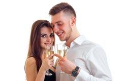 Pares novos bonitos que guardam vidros de vinho e que sorriem no fundo branco Imagem de Stock