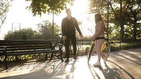 Pares novos bonitos que montam suas bicicletas no parque ou no bulevar vazio da cidade no verão Pare e sente-se no banco vídeos de arquivo