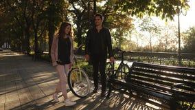 Pares novos bonitos que montam suas bicicletas no parque vazio da cidade Pare e sente-se no banco e no abraço Pares Loving filme
