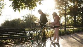 Pares novos bonitos que montam suas bicicletas no parque vazio da cidade Pare e sente-se no banco e no abraço Pares Loving vídeos de arquivo