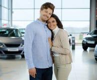 Pares novos bonitos que olham um carro novo na sala de exposições do negócio Imagem de Stock