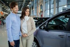 Pares novos bonitos que olham um carro novo na sala de exposições do negócio Imagem de Stock Royalty Free