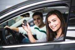 Pares novos bonitos que sentam-se nos assentos dianteiros de seu carro novo quando mulher que mostra chaves e sorriso fotografia de stock