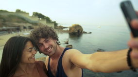 Pares novos bonitos que tomam selfies na praia video estoque