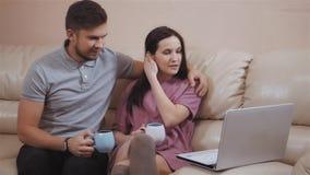 Pares novos bonitos usando o portátil em casa que senta-se no sofá de couro video estoque