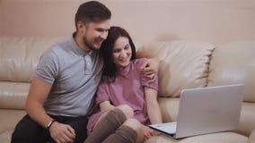 Pares novos bonitos usando o portátil em casa que senta-se no sofá de couro, usando Skype filme