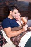 Pares novos bonitos usando um PC da tabuleta na cama Foto de Stock
