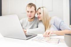 Pares novos bonitos, usando um portátil e escolhendo um apartamento novo fotos de stock royalty free