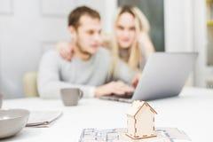 Pares novos bonitos, usando um port?til e escolhendo um apartamento novo E imagens de stock royalty free
