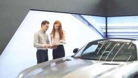 Pares novos caucasianos que escolhem o carro luxuoso no auto negócio que olha as características do interior e do carro filme