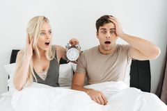 Pares novos chocados que sentam-se na cama com boca aberta e que guardam o despertador Foto de Stock Royalty Free
