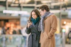 Pares novos com Apple Iphone na estação central de Utrecht, Países Baixos Fotografia de Stock