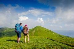 Pares novos com as trouxas que caminham nas montanhas Imagens de Stock