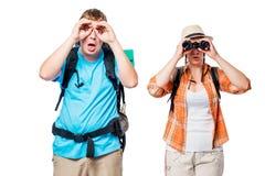 Pares novos com as trouxas que olham nos binóculos no branco Fotografia de Stock