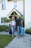Pares novos com a bagagem que anda longe de uma casa Imagem de Stock Royalty Free