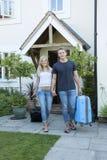 Pares novos com a bagagem que anda longe de uma casa Foto de Stock