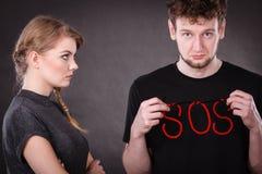 Pares novos com coração quebrado e palavra do SOS Imagens de Stock