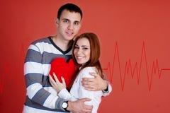 Pares novos com coração vermelho Imagens de Stock Royalty Free